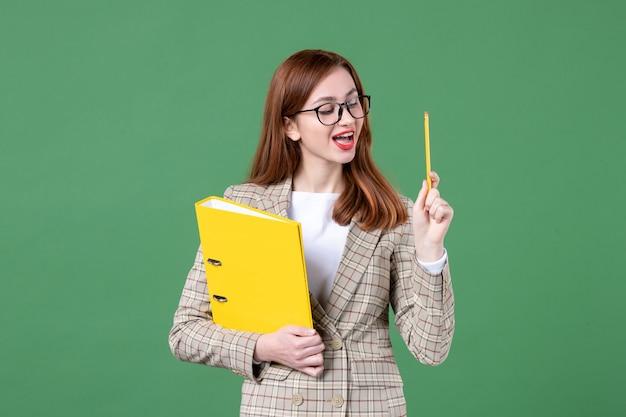 緑に黄色のファイルと鉛筆を保持している女教師の肖像画