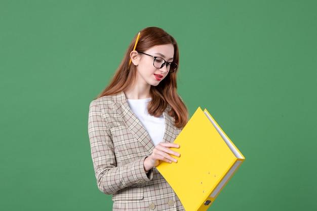 緑に黄色のファイルを保持している女教師の肖像画