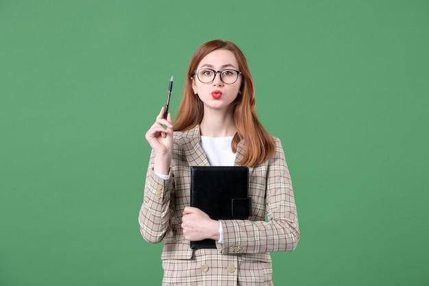 緑のメモ帳とペンでスーツの女教師の肖像画