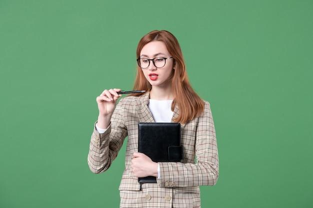 緑のメモ帳とスーツの女教師の肖像画