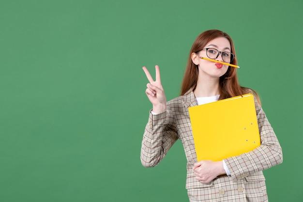 Портрет учительницы с напильником и карандашом вокруг рта на зеленом