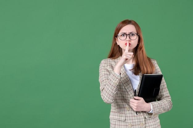 緑の上で静かにするように頼むメモ帳を持つ女性教師の肖像画