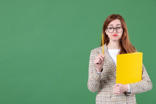 Портрет учительницы с желтым документом и карандашом на зеленом