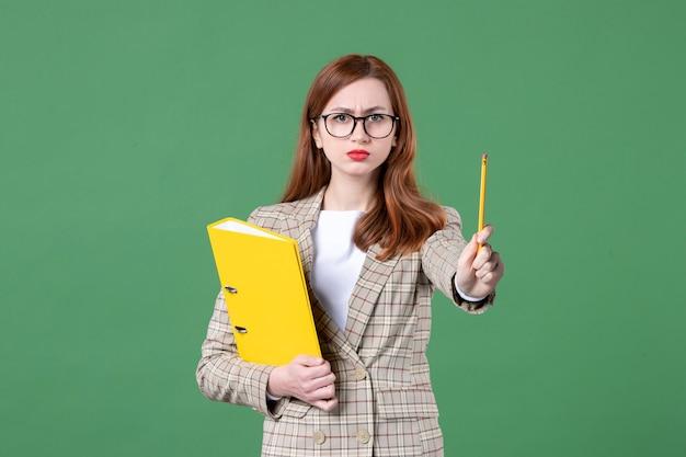 Портрет учительницы с желтыми файлами, рассерженная на зеленом
