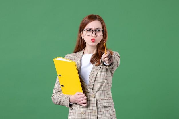 緑に黄色のファイルと女性教師の肖像画