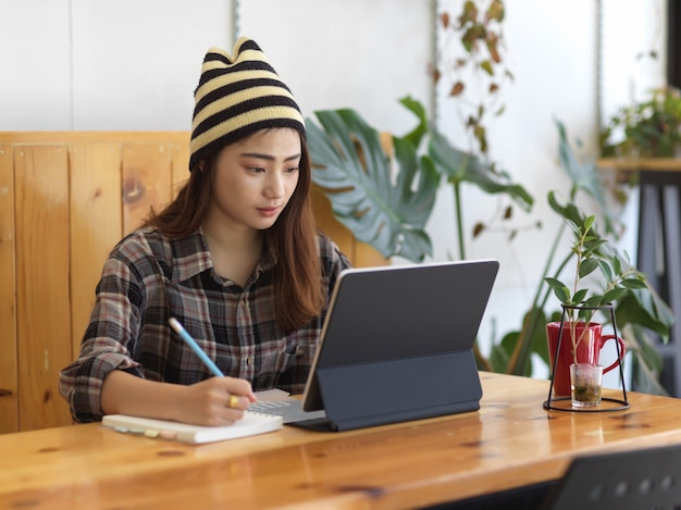 Портрет девушки-подростка, делающей домашнее задание с цифровым планшетом на деревянном столе