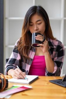 居間でオンライン勉強しながらコーヒーを飲む女性のティーンエイジャーの肖像画