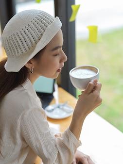 Портрет девушки-подростка, пьющего кофе, расслабленно сидя в кафе