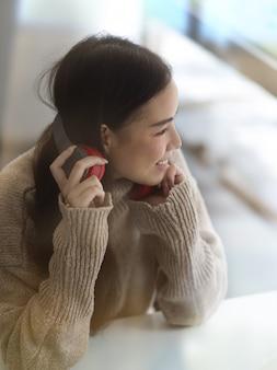 Портрет девушки-подростка в свитере с наушниками, улыбаясь и глядя в камеру, сидя в кафе