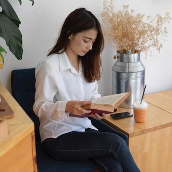 リビングルームの肘掛け椅子に座って本を読んでいる10代の女性の肖像