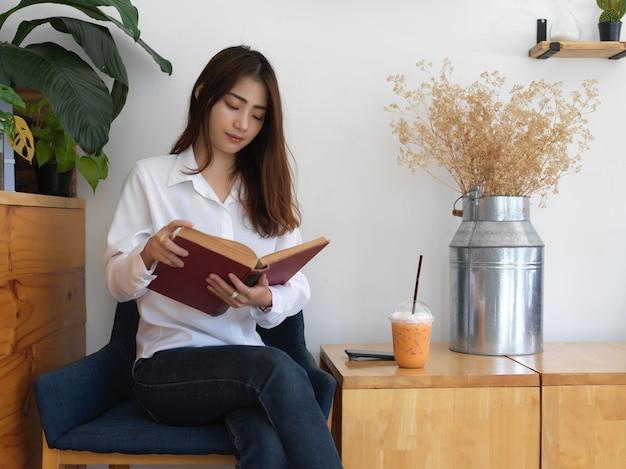 Портрет девушки-подростка, читающей книгу, сидя на кресле в гостиной