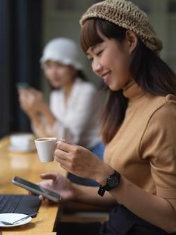 カフェで彼女の友人と座っている間コーヒーとスマートフォンでリラックスする女性のティーンエイジャーの肖像画