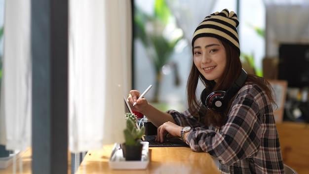 Портрет девушки-подростка, улыбающейся и смотрящей в камеру, расслабляясь с наушниками и планшетом