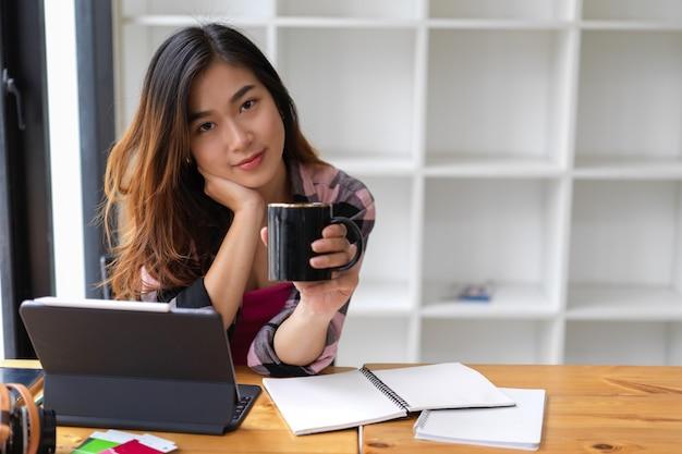 カメラに微笑んで、勉強のテーブルでリラックスしながらコーヒーカップを保持している女性のティーンエイジャーの肖像画