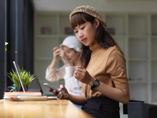 スマートフォンを使用してカフェで宿題をしながらコーヒー休憩を取る女性のティーンエイジャーの肖像画