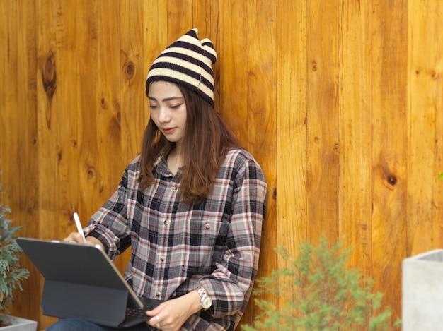 Портрет девушки-подростка, работающей с цифровым планшетом на коленях, сидя в кафе