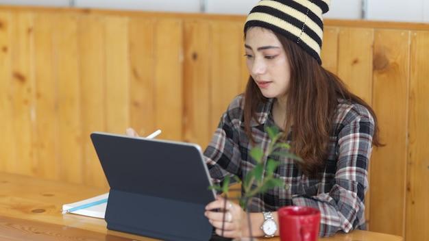 커피 잔과 식물 꽃병 나무 테이블에 디지털 태블릿을 사용하는 여성 십대의 초상화