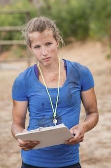 ブートキャンプの障害物コース中にクリップボードを保持している女性トレーナーの肖像画