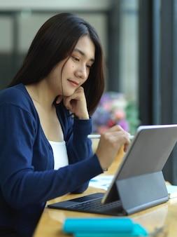 Портрет студентки университета, делающей домашнее задание с цифровым планшетом в кафе