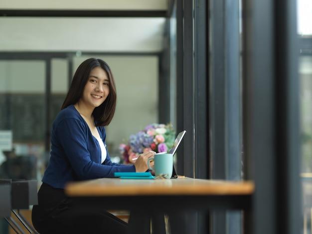 Портрет студентки университета, улыбаясь в камеру, выполняя задание в кафе