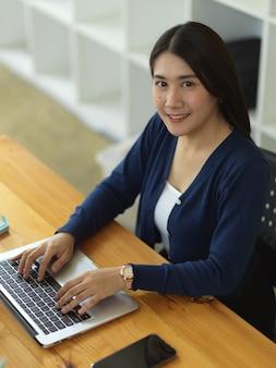 Портрет студентки университета, улыбаясь в камеру, выполняя задание с ноутбуком в библиотеке