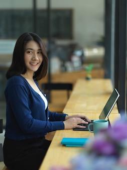 Портрет студентки университета, улыбаясь в камеру, выполняя задание с планшетом в кафе
