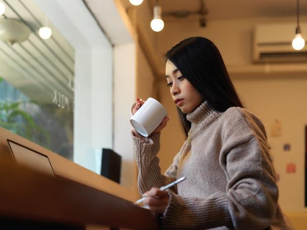 Портрет студентки университета отдыхает с горячим напитком во время выполнения задания в кафе