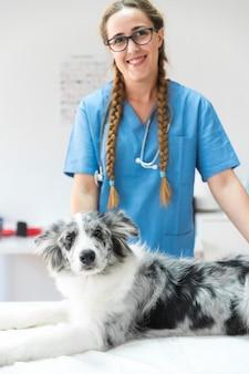 Портрет женщины-ветеринар с собакой, лежащей на столе в клинике