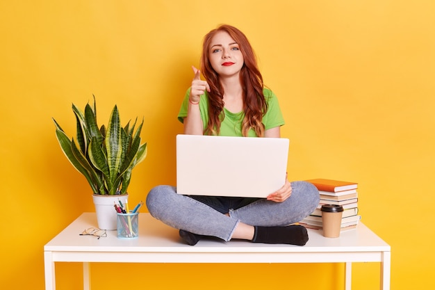 Портрет девушки с ноутбуком на ногах, глядя на указывая вперед