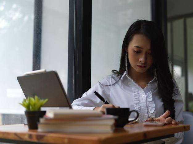 Портрет работницы, сосредоточенной на своей работе со смартфоном, канцелярскими принадлежностями и ноутбуком