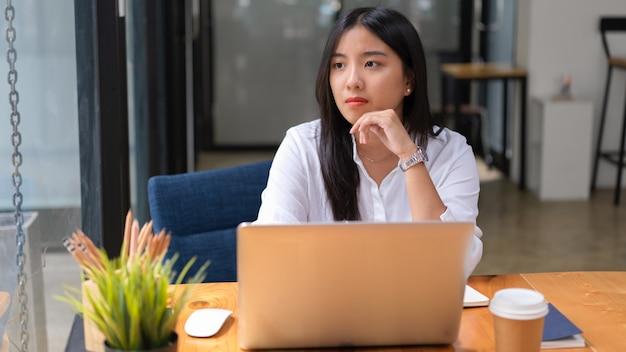 Портрет работницы в белой рубашке, думающей о своей работе и смотрящей в окно офиса