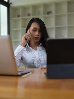 사무실 방에서 디지털 장치로 작업하는 동안 전화로 얘기하는 여성 노동자의 초상화