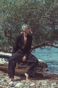反転した釣り船の端に座っている裸の体の上に黒いスーツを着たフェミニンなブロンドの女の子の肖像画