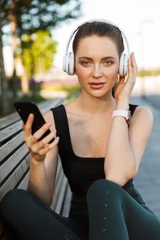 Портрет женственной спортсменки в спортивном костюме, держащей смартфон и слушающей музыку в наушниках, сидя на скамейке в городском парке