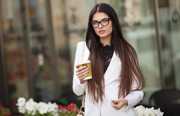 ビジネスセンターへの金融大会に歩いている間一杯のコーヒーを手で保持している金融専門の実業家の肖像画。
