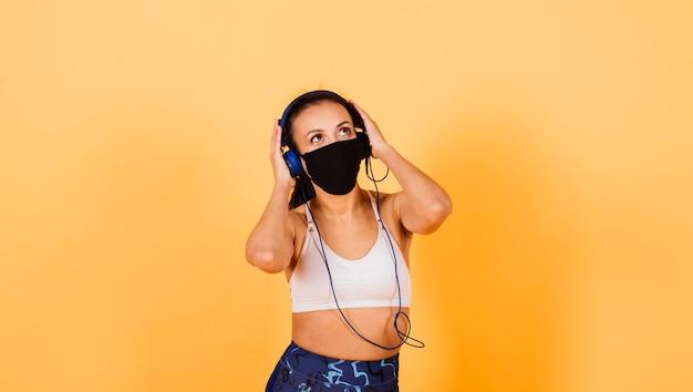 얼굴 마스크를 쓰고 맞는 아프리카 여자의 초상화입니다. 노란색 바탕에 피트 니스 착용에 스포티 한 여자입니다.