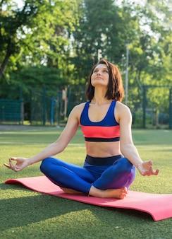 Портрет подтянутой и спортивной молодой женщины, делающей упражнения на растяжку, йогу или пилатес в парке раннего утра. городская летняя тренировка.