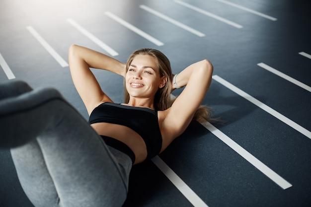 クランチをしている完璧な体を持つフィット女性の肖像画。フィットネスコーチになるには献身が必要です。健康的な生活の概念。