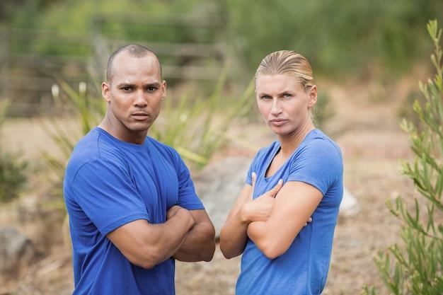 ブートキャンプのトレーニング中に腕を組んで立っているフィットの男性と女性の肖像画