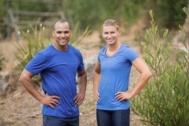 ブートキャンプのトレーニング中に腰に手を置いて立っているフィットの男性と女性の肖像画