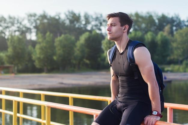 座っていると川の近くに屋外で休んでフィット男ランナーの肖像画。