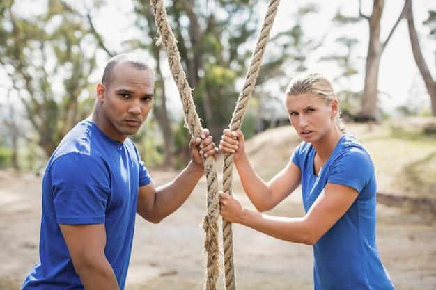 ブートキャンプトレーニング中にロープを保持しているフィットの人々の肖像画