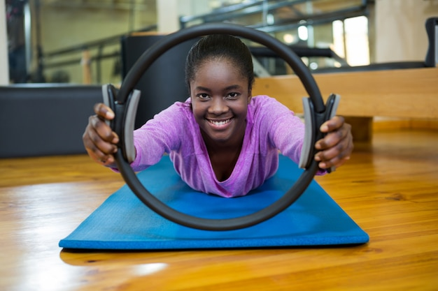 Портрет подходящей женщины, тренирующейся с кольцом пилатеса в фитнес-студии