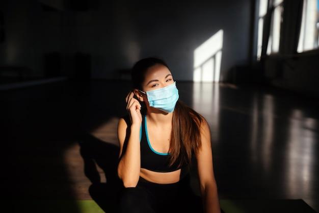 얼굴 보호 마스크를 씌우고 맞는 여자의 초상화. 얼굴 마스크를 착용하는 스포티 한 여자.
