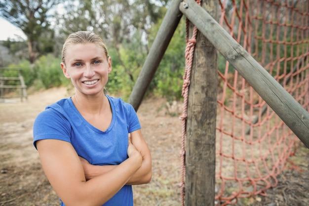 ブートキャンプのトレーニング中に腕を組んで立っているフィット女性の肖像画