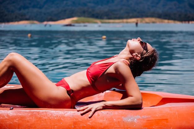 タイの美しい湖でカヤックでリラックスしたビキニでフィットする若い白人観光客の女性の肖像画。晴れた日を楽しんで休暇中の女性。