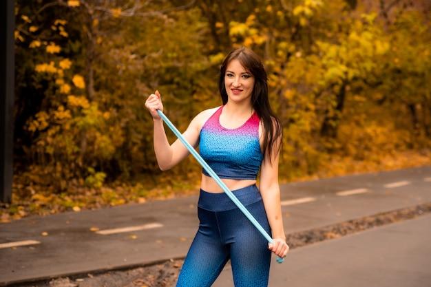 Портрет подходящей молодой женщины с скакалкой в осеннем парке. фитнес женский холдинг скакалка перед ее разминкой на открытом воздухе. на ней яркая спортивная одежда. спортивная девушка улыбается