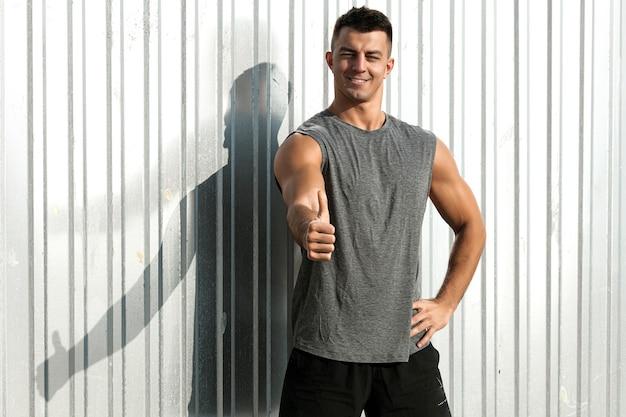 親指を上に向けるジェスチャーでフィットネスアスリートの男の肖像画。素敵な筋肉質の男。