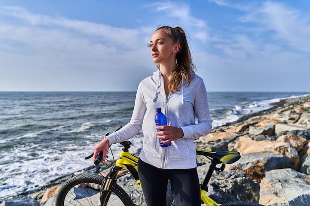 Портрет фитнес спортсменка с желтым велосипедом