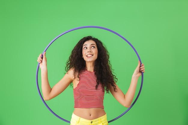 Портрет фитнес-женщины 20-х годов в летней одежде, делающей упражнения с обручем во время гимнастики на зеленой стене